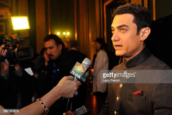 Aamir Kahn speaks to a reporter at the 2013 America Abroad Media Awards Dinner at Andrew W Mellon Auditorium on October 28 2013 in Washington DC
