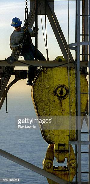 AAplatformhang0118RL––Joe Garcia a floor hand with Pool Offshore hangs in the air while lubricating the drill rig on the platform Ellen as the sun...
