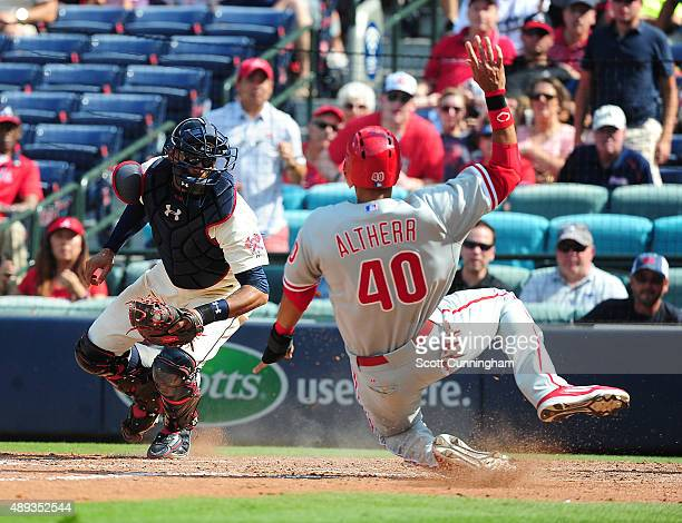 Aaron Altherr of the Philadelphia Philiies scores a ninth inning run against Christian Bethancourt of the Atlanta Braves at Turner Field on September...