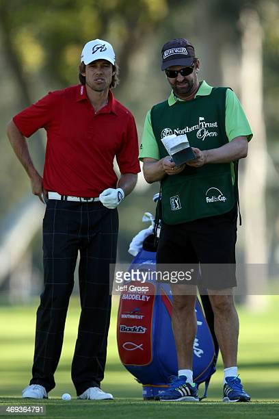 Aaron Baddeley of Australia discusses his second shot on the 2nd hole with his caddie Anthony Knight in the second round of the Northern Trust Open...
