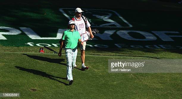 Aaron Baddeley of Australia walks with his caddie Anthony Knight to the 18th green during the third round of the TOUR Championship at East Lake Golf...