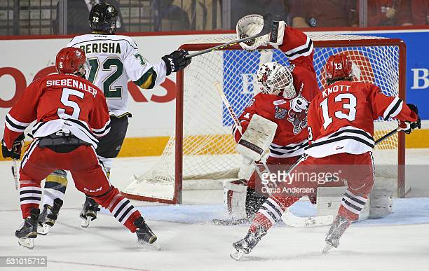 Aaron Berisha of the London Knights has a scoring attempt knocked away by Alex Nedeljkovic of the Niagara IceDogs during Game Four of the OHL...