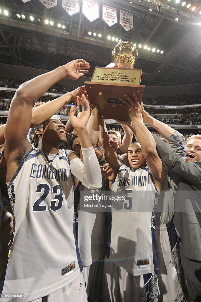Aaron Bowen #23 and Markel Starks #5 of the Georgetown Hoyas raise the regular Big East Championship trophy after a college basketball game against the Syracuse Orange on March 9, 2013 at the Verizon Center in Washington, DC. The Hoyas won 61-39.