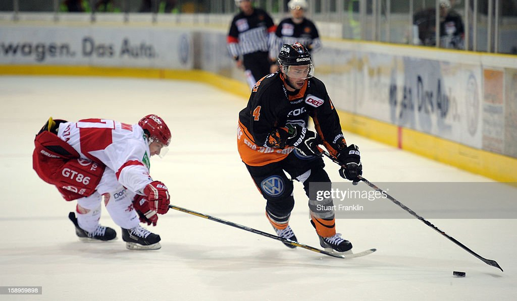 Aaron Brocklehurst of Wolfsburg challenges for the puck with Marcel Ohmann of Cologne during the DEL match between Grizzly Adams Wolfsburg and Kolner Haie at the Volksbank BraWo Eisarena on January 4, 2013 in Wolfsburg, Germany