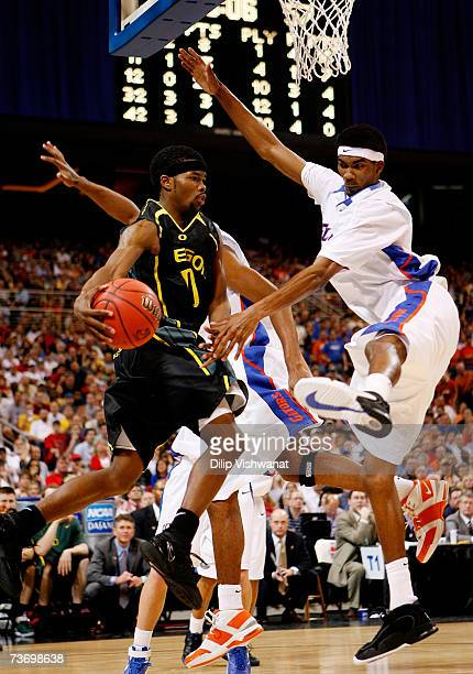 Aaron Brooks of the Oregon Ducks drives around Corey Brewer of the Florida Gators during the midwest regionals of the NCAA Men's Basketball...