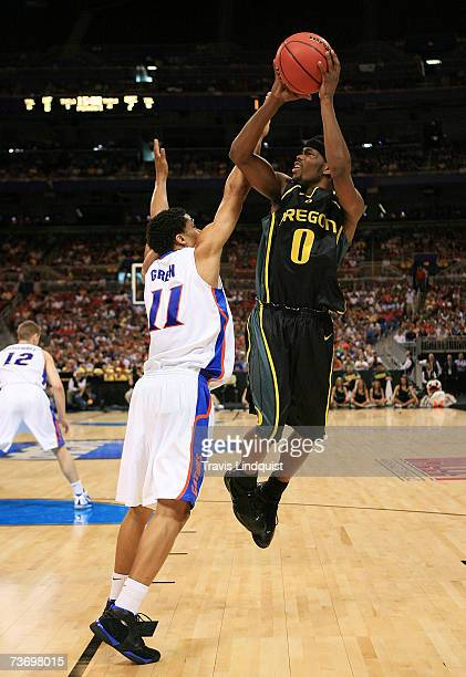 Aaron Brooks of the Oregon Ducks puts up a shot over Taurean Green of the Florida Gators during the midwest regionals of the NCAA Men's Basketball...