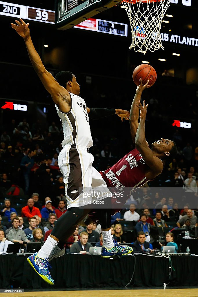 Aaron Brown of the Saint Joseph's Hawks is fouled by Opeyemi Olomo of the St Bonaventure Bonnies during the Second Round of the Atlantic 10...