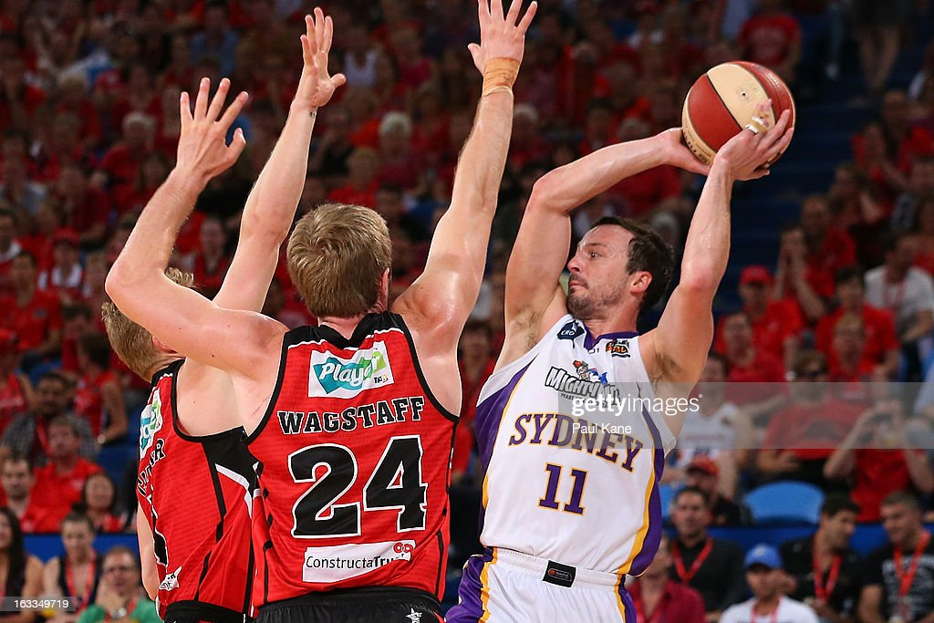 Aaron Bruce of the Kings looks to pass the ball against Rhys Carter and Jesse Wagstaff of the Wildcats during the round 22 NBL match between the Perth Wildcats and the Sydney Kings at Perth Arena on March 8, 2013 in Perth, Australia.