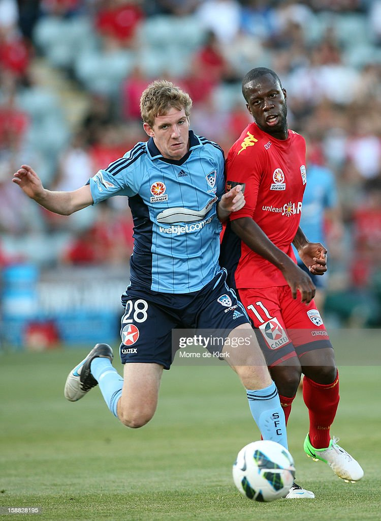 Aaron Calver of Sydney competes with <a gi-track='captionPersonalityLinkClicked' href=/galleries/search?phrase=Bruce+Djite&family=editorial&specificpeople=775797 ng-click='$event.stopPropagation()'>Bruce Djite</a> of Adelaide during the round 14 A-League match between Adelaide United and Sydney FC at Hindmarsh Stadium on December 31, 2012 in Adelaide, Australia.