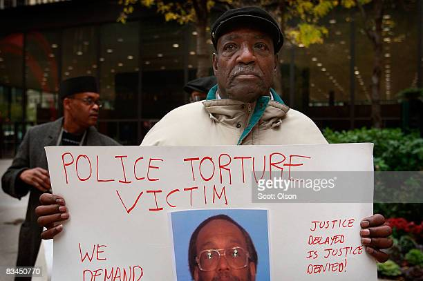 Aaron Cheney demonstrates outside the federal courthouse where former Chicago Police Commander Jon Burge was attending a hearing on charges he...