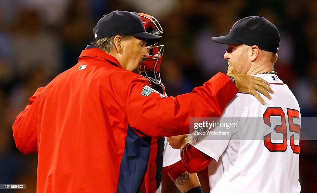 Aaron Cook #35 of the Boston Red Sox talks to teammate Jarrod Saltalamacchia #39 and pitching coach Randy Niemann #68 at the mound during the game against the New York Yankees on September 12, 2012 at Fenway Park in Boston, Massachusetts.