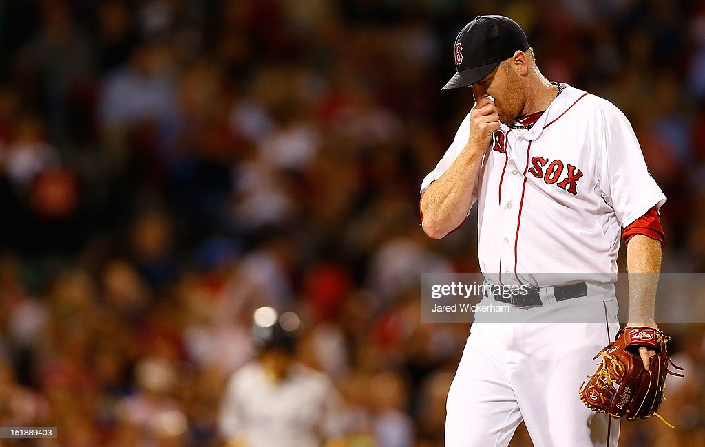 Aaron Cook #35 of the Boston Red Sox wipes the sweat off of his face after giving up three runs in the fourth inning against the New York Yankees during the game on September 12, 2012 at Fenway Park in Boston, Massachusetts.