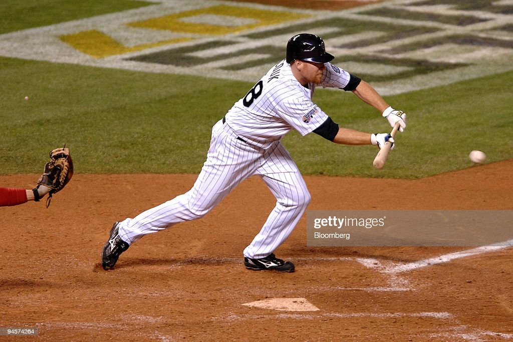 Aaron Cook of the Colorado Rockies lays down a bunt single while batting against the Boston Red Sox during Game 4 of the Major League Baseball World...