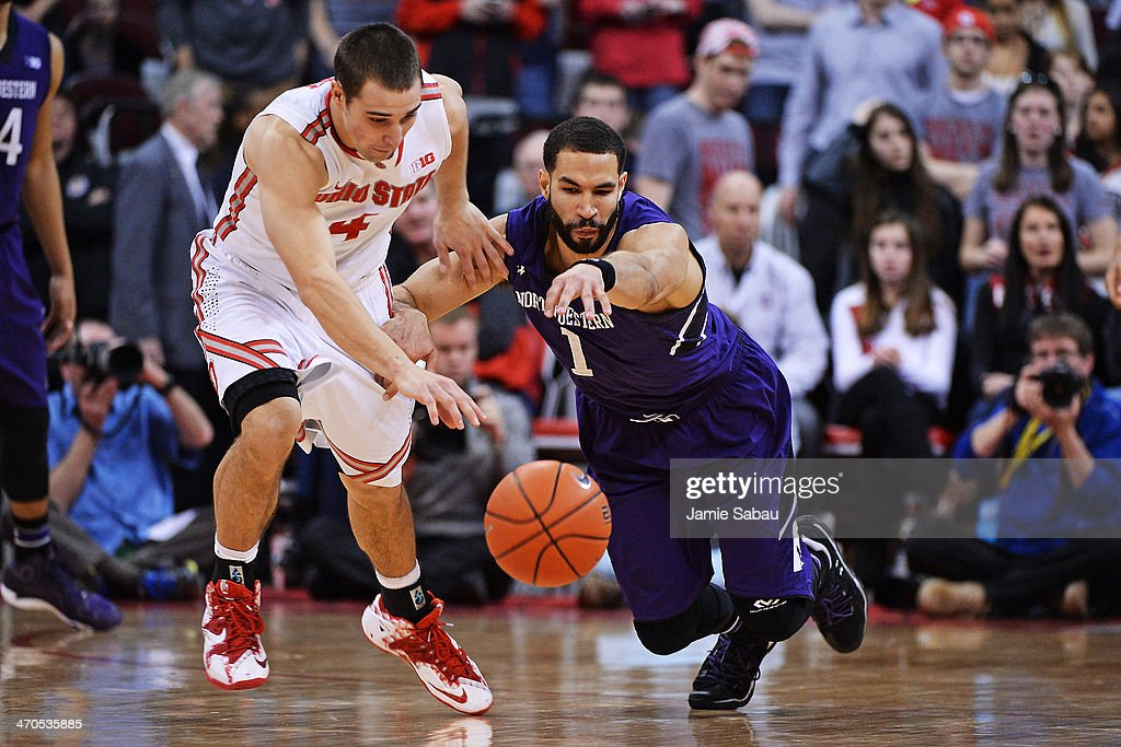 Aaron Craft #4 of the Ohio State Buckeyes and Drew Crawford #1 of the Northwestern Wildcats battle for control of a loose ball in the second half on February 19, 2014 at Value City Arena in Columbus, Ohio. Ohio State defeated Northwestern 76-60.