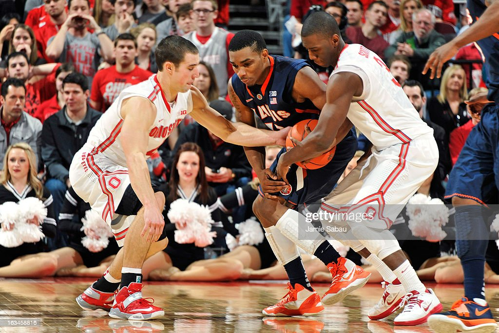 Aaron Craft #4 of the Ohio State Buckeyes and Shannon Scott #3 of the Ohio State Buckeyes apply pressure to Tracy Abrams #13 of the Illinois Fighting Illini forcing a turnover in the first half on March 10, 2013 at Value City Arena in Columbus, Ohio. Ohio State defeated Illinois 68-55.