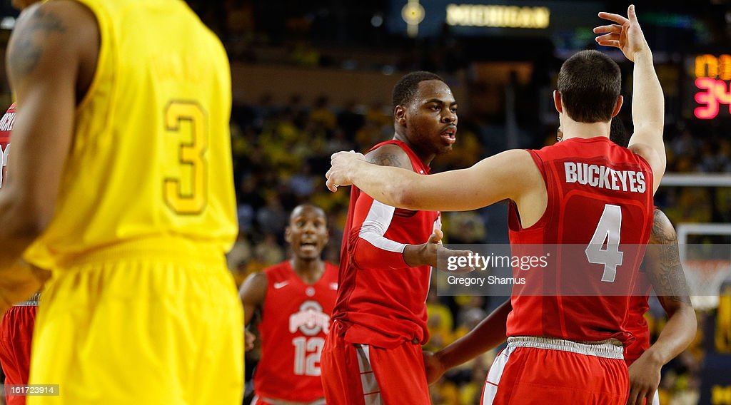 Aaron Craft #4 of the Ohio State Buckeyes and teammates meet up during a break against the Michigan Wolverines at Crisler Center on February 5, 2013 in Ann Arbor, Michigan. Michigan won the game 76-74 in overtime.