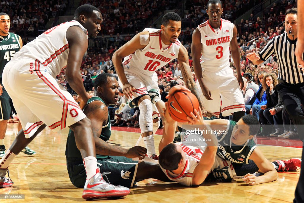 <a gi-track='captionPersonalityLinkClicked' href=/galleries/search?phrase=Aaron+Craft&family=editorial&specificpeople=7348782 ng-click='$event.stopPropagation()'>Aaron Craft</a> #4 of the Ohio State Buckeyes and Travis Trice #20 of the Michigan State Spartans wrestle for a loose ball in the first half on February 24, 2013 at Value City Arena in Columbus, Ohio. Michigan State retained possession.