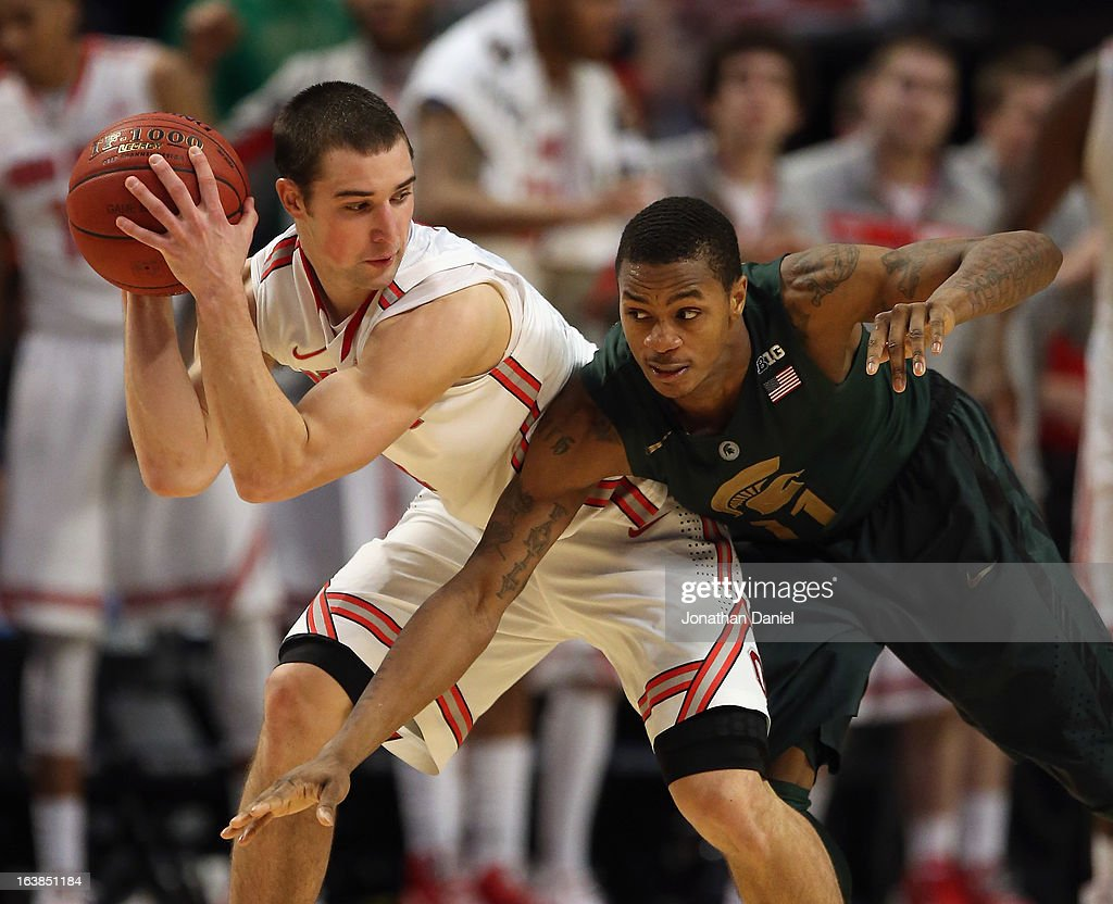 <a gi-track='captionPersonalityLinkClicked' href=/galleries/search?phrase=Aaron+Craft&family=editorial&specificpeople=7348782 ng-click='$event.stopPropagation()'>Aaron Craft</a> #4 of the Ohio State Buckeyes controls the ball against Keith Appling #11 of the Michigan State Spartans during a semifinal game of the Big Ten Basketball Tournament at the United Center on March 16, 2013 in Chicago, Illinois. Ohio State defeats Michigan State 61-58.