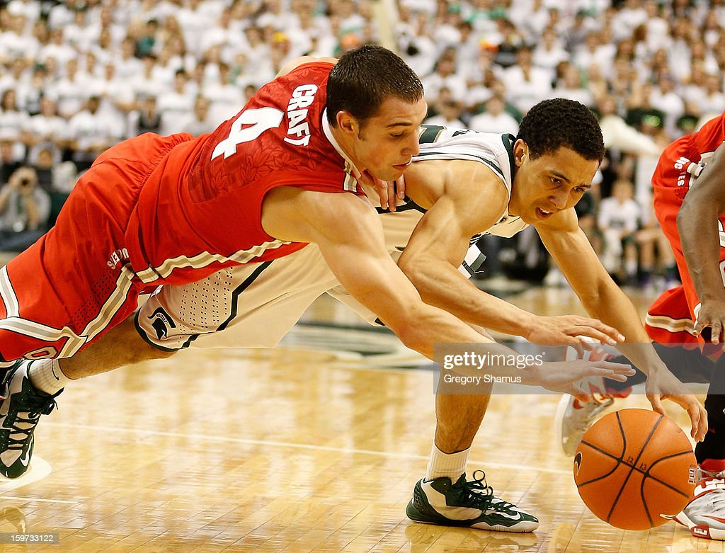 Aaron Craft #4 of the Ohio State Buckeyes dives for a first-half loose ball against Travis Trice #20 of the Michigan State Spartans at the Jack Breslin Center on January 19, 2013 in East Lansing, Michigan.