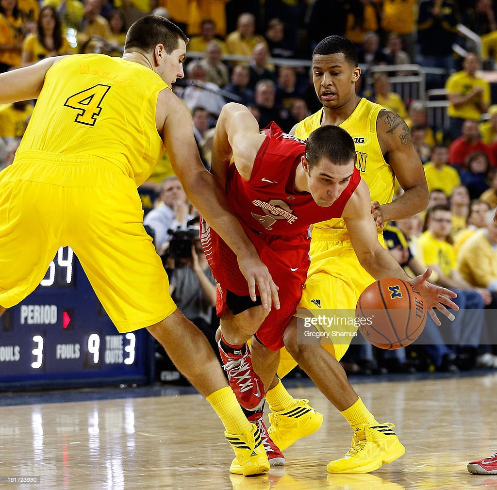 Aaron Craft #4 of the Ohio State Buckeyes drives around Mitch McGary #4 of the Michigan Wolverines at Crisler Center on February 5, 2013 in Ann Arbor, Michigan. Michigan won the game 76-74 in overtime.