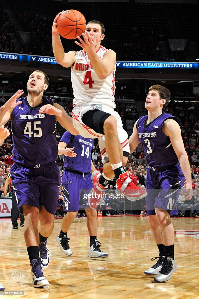 <a gi-track='captionPersonalityLinkClicked' href=/galleries/search?phrase=Aaron+Craft&family=editorial&specificpeople=7348782 ng-click='$event.stopPropagation()'>Aaron Craft</a> #4 of the Ohio State Buckeyes drives to the basket to lay in two points past the defense of Nikola Cerina #45 and Dave Sobolweski #3 of the Northwestern Wildcats in the second half on February 14, 2013 at Value City Arena in Columbus, Ohio. Ohio State defeated Northwestern 69-59.
