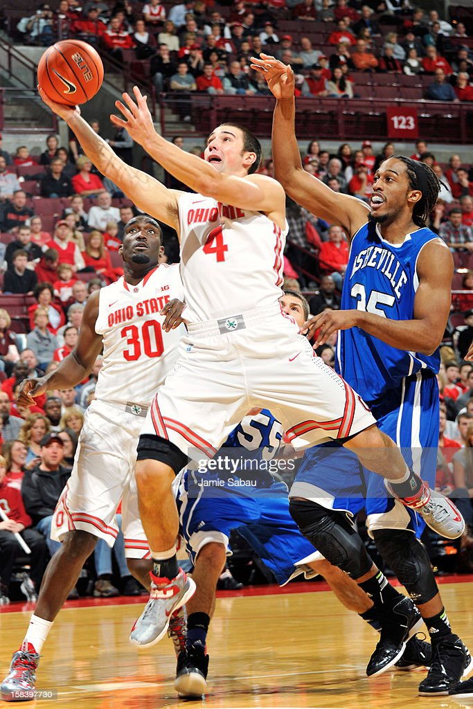 <a gi-track='captionPersonalityLinkClicked' href=/galleries/search?phrase=Aaron+Craft&family=editorial&specificpeople=7348782 ng-click='$event.stopPropagation()'>Aaron Craft</a> #4 of the Ohio State Buckeyes flies past Jon Nwannunu #35 of the UNC Asheville Bulldogs in the first half for a layup on December 15, 2012 at Value City Arena in Columbus, Ohio. Ohio State defeated UNC Asheville 90-72.