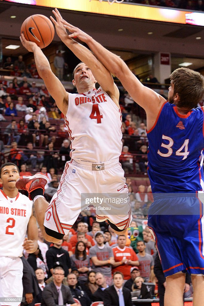 <a gi-track='captionPersonalityLinkClicked' href=/galleries/search?phrase=Aaron+Craft&family=editorial&specificpeople=7348782 ng-click='$event.stopPropagation()'>Aaron Craft</a> #4 of the Ohio State Buckeyes lays in two points over Tony Wroblicky #34 of the American University Eagles in the second half on November 20, 2013 at Value City Arena in Columbus, Ohio. Ohio State defeated American 63-52.