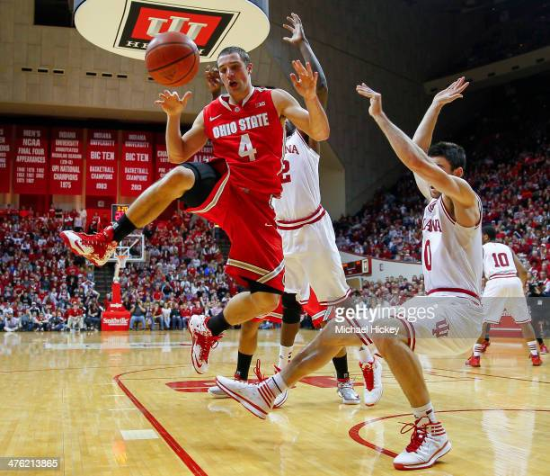 Aaron Craft of the Ohio State Buckeyes loses the ball while shooting as Will Sheehey of the Indiana Hoosiers falls to the ground at Assembly Hall on...