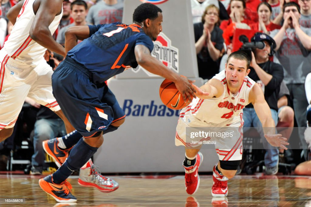 Aaron Craft #4 of the Ohio State Buckeyes lunges in to knock the ball loose from D.J. Richardson #1 of the Illinois Fighting Illini in the second half on March 10, 2013 at Value City Arena in Columbus, Ohio. Ohio State defeated Illinois 68-55.