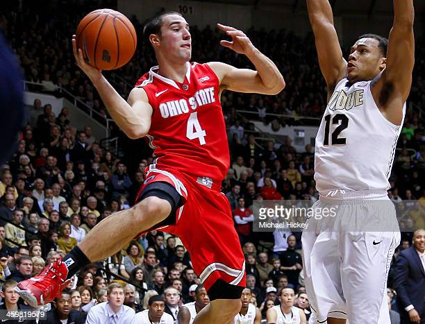 Aaron Craft of the Ohio State Buckeyes passes the ball off as Bryson Scott of the Purdue Boilermakers defends at Mackey Arena on December 31 2013 in...