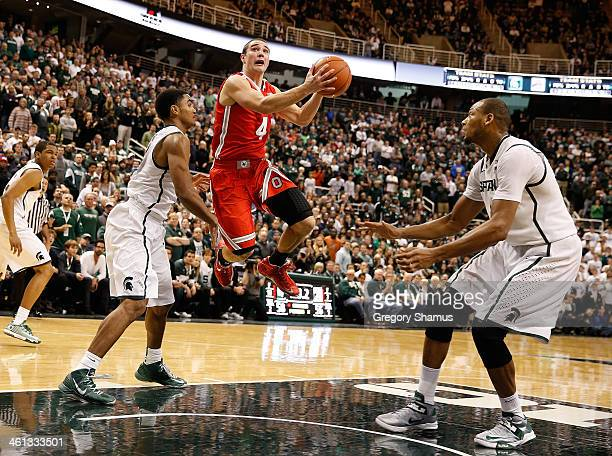 Aaron Craft of the Ohio State Buckeyes tries to split the defense of Gary Harris and Adreian Payne of the Michigan State Spartans during the second...