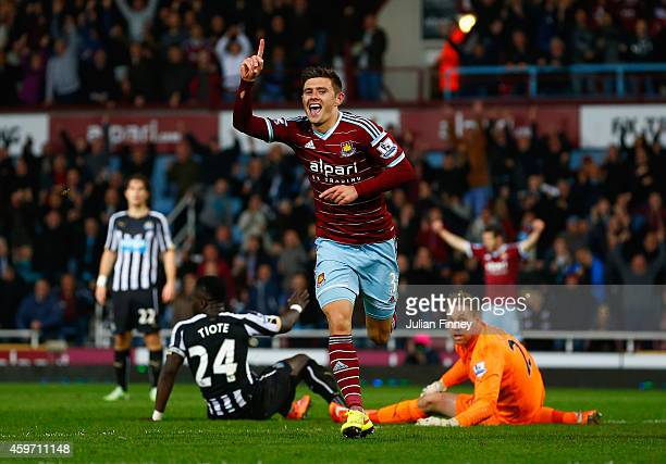 Aaron Cresswell of West Ham celebrates scoring opening goal past Robert Elliot of Newcastle United during the Barclays Premier League match between...