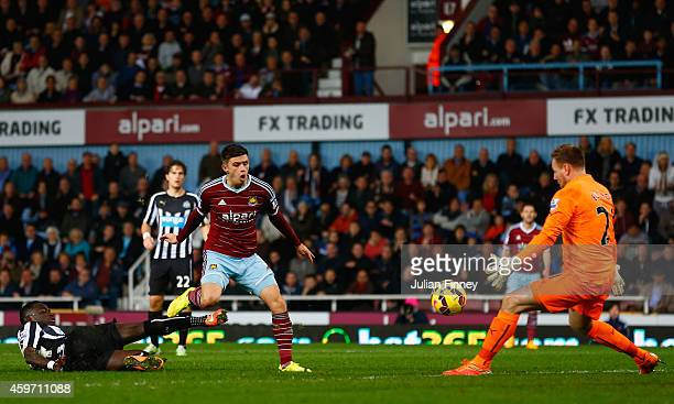 Aaron Cresswell of West Ham scores the opening goal past Robert Elliot of Newcastle United during the Barclays Premier League match between West Ham...