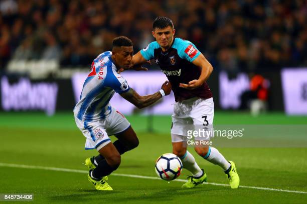 Aaron Cresswell of West Ham United and Rajiv van La Parra of Huddersfield Town battle for the ball during the Premier League match between West Ham...
