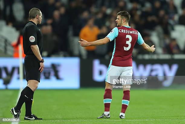 Aaron Cresswell of West Ham United argues with assistant referee Adrian Holmes over the red card shown to Sofiane Feghouli of West Ham United during...