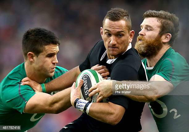 Aaron Cruden of the All Blacks is tackled by Conor Murray and Gordon D'Arcy of Ireland during the International match between Ireland and the New...
