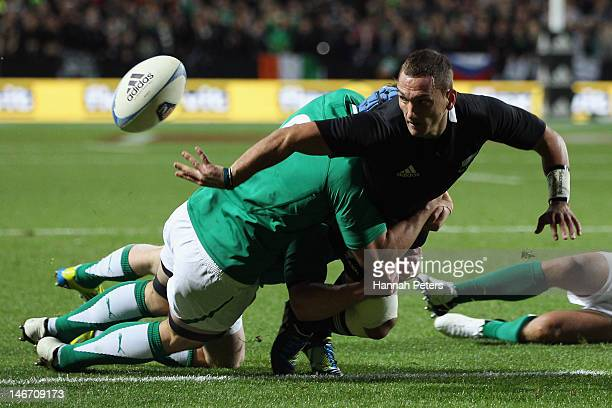 Aaron Cruden of the All Blacks offloads the ball during the International Test Match between New Zealand and Ireland at Waikato Stadium on June 23...