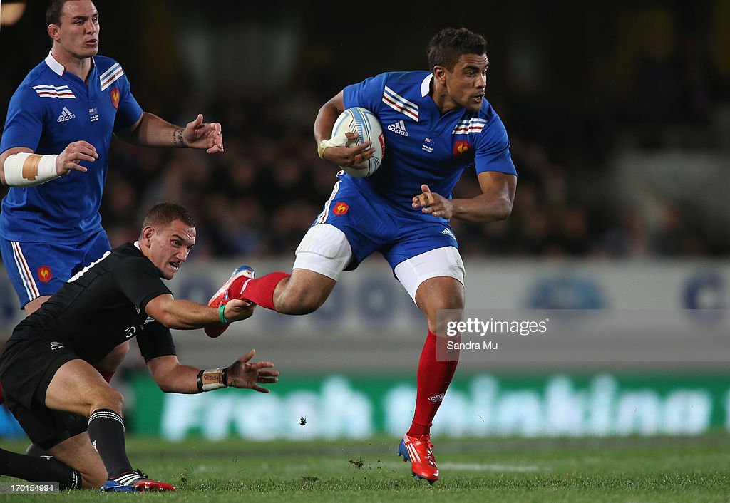 Aaron Cruden of the All Blacks takes Wesley Fofana of France by the foot during the first test match between the New Zealand All Blacks and France at Eden Park on June 8, 2013 in Auckland, New Zealand.