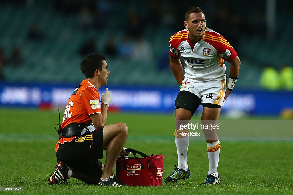 Aaron Cruden of the Chiefs grimaces as he stands after receiving attenbtion from the trainer during the round 10 Super Rugby match between the Waratahs and the Chiefs at Allianz Stadium on April 19, 2013 in Sydney, Australia.