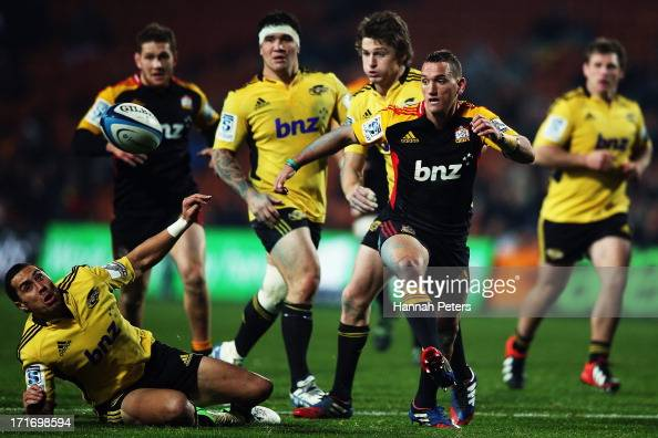 Aaron Cruden of the Chiefs kicks the ball through past Chris Smylie of the Hurricanes during the round 18 Super Rugby match between the Chiefs and...