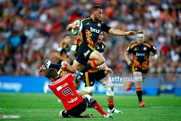 Aaron Cruden of the Chiefs leaps over the tackle of Mitchell Drummond of the Crusaders during the round three Super Rugby match between the Chiefs...