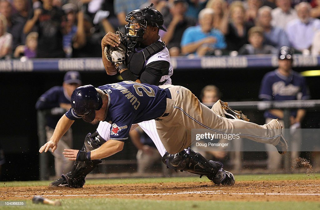 Aaron Cunningham #28 of the San Diego Padres is tagged out at home by catcher <a gi-track='captionPersonalityLinkClicked' href=/galleries/search?phrase=Miguel+Olivo&family=editorial&specificpeople=209185 ng-click='$event.stopPropagation()'>Miguel Olivo</a> #21 of the Colorado Rockies for the final out of the third inning as Cunningham tried to score on an Adrian Gonzalez base hit at Coors Field on September 13, 2010 in Denver, Colorado.