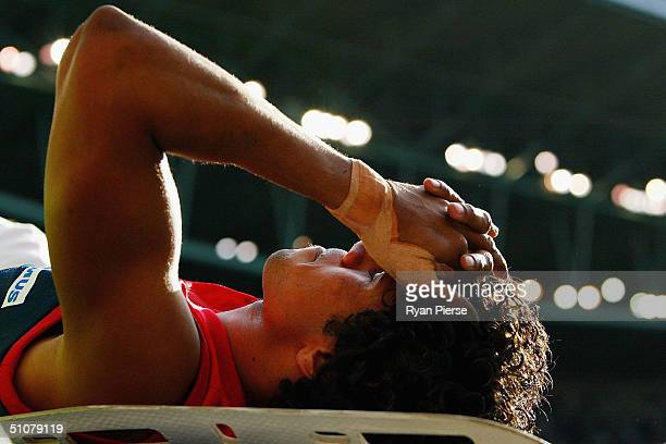 Aaron Davey for the Demons is carried off the ground after injuring his leg during the round sixteen AFL match between The Melbourne Demons and The...