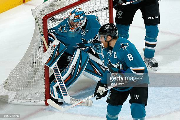 Aaron Dell and Joe Pavelski of the San Jose Sharks watch the puck during a NHL game against the Carolina Hurricanes at SAP Center at San Jose on...