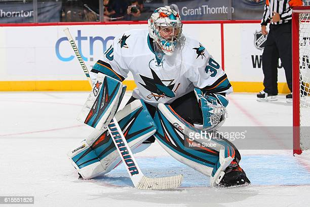 Aaron Dell and Paul Martin of the San Jose Sharks defends the net against the New York Islanders at the Barclays Center on October 18 2016 in...