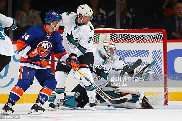 Aaron Dell and Paul Martin of the San Jose Sharks defends the net against Thomas Hickey of the New York Islanders at the Barclays Center on October...