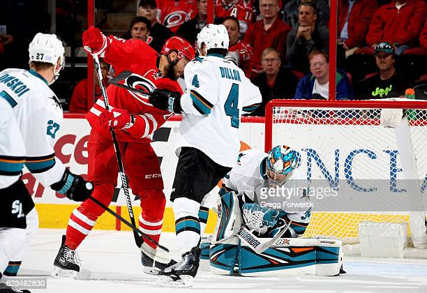 Aaron Dell of the San Jose Sharks absorbs a shot on goal as teammate Brenden Dillon defends ands Viktor Stalberg looks to deflect the puck in during...