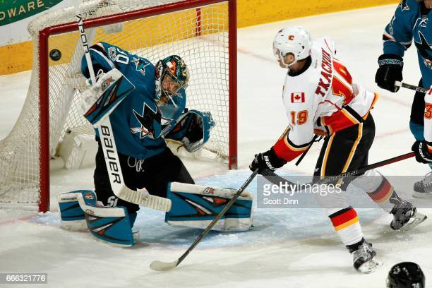 Aaron Dell of the San Jose Sharks blocks the puck as Matthew Tkachuk of the Calgary Flames looks on at SAP Center at San Jose on April 8 2017 in San...