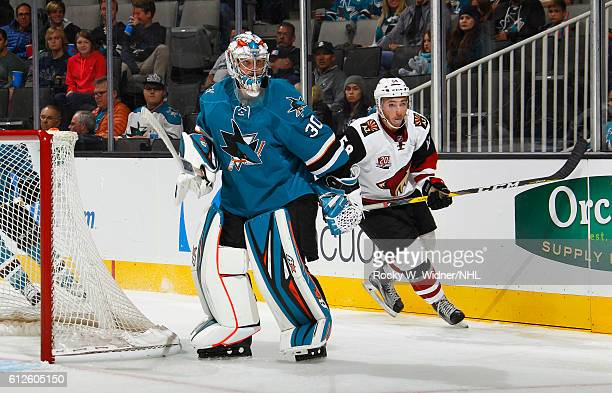 Aaron Dell of the San Jose Sharks defends the net against Michael Bunting of the Arizona Coyotes at SAP Center on September 30 2016 in San Jose...
