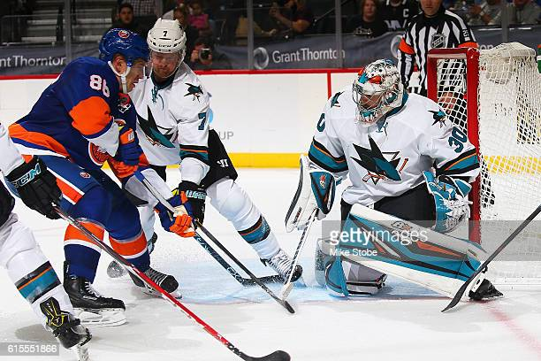 Aaron Dell of the San Jose Sharks defends the net against Nikolay Kulemin of the New York Islanders at the Barclays Center on October 18 2016 in...